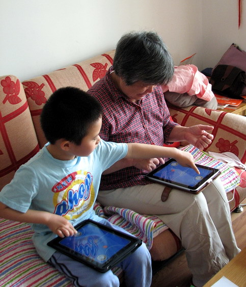 yoyo is playing multi-player ipad game with his grandma.