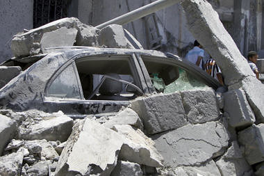 In this photo taken on a tour, a damaged car lies underneath rubble opposite a damaged residential building in Tripoli, Libya, Sunday, June 19, 2011. The US and Europe are justifying the carnage. by Pan-African News Wire File Photos