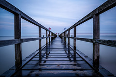 Winter's Bridge // Wyk (//Sebastian) Tags: cold wet blue bridge water wood plank flag wave wavingflags longexposure monotone clouds boat passing stripes northsea sand beach sad moody symmetry horizon wyk fhr germany foehr autumn fall winter