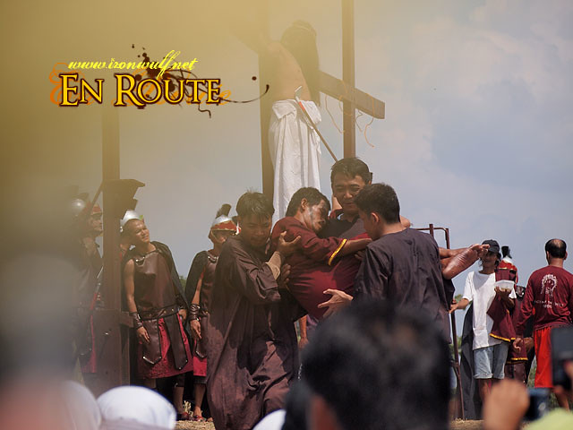 One of the performers nailed to the cross is carried over to the ambulance