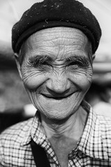 Portrait of an old blue Hmong man (Yan Lerval) Tags: dongvan hagiang portrait vietnam beret black blackwhite bluehmong dust ethnic eyebrows hat hilltribe man old shirt smile tribe vertical wrinkles hgiang vn