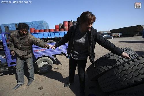 3月27日,河北沧州泊头货场,郭伟明的妻子一边查看挑好的旧轮胎,一边把钱递到商贩手里。一辆大货车一年磨损下来,18个轮胎要换个遍。由于轮胎价格太高,他们只能花3300元先买4个旧轮胎换上,买新的则要8000多元。