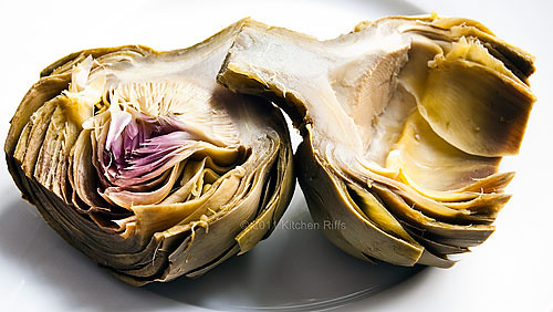 view of two artichoke halves, one with choke and inner leaves intact, other with choke and inner leaves scooped out