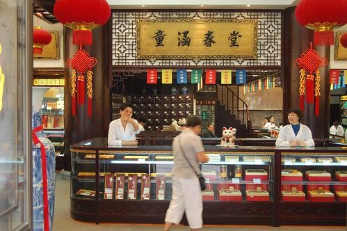 An einem alten Tresen stehen zwei Apothekerinnen in einer Apotheke in Shanghai. In der Auslage sind chinesische Arzneimittel zu sehen, Oben hängen rote Lampions und grosse chinesische Schriftzeichen