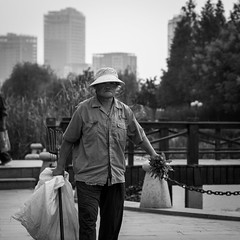 Like a man (Go-tea ) Tags: canon eos 100d 5omm bw bnw black blackwhite blackandwhithe white outside outdoor hurban city street china chinese asian asia qingdao huangdao park portrait people woman old walking bad carried man hat cap shadow shirt stick wood buildings towers background plant wild