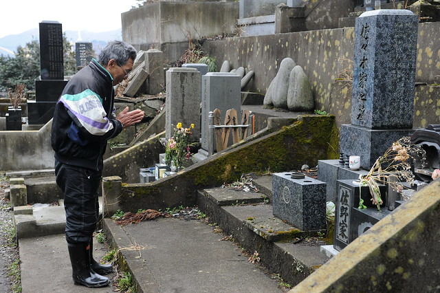 Japanese Man Prays at the Tomb of Dead Family Member