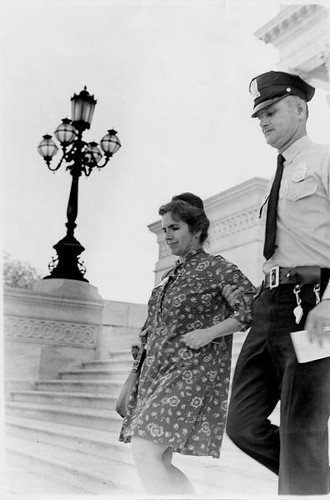 Paley, in a housedress, being escorted down some stairs by a police officer