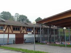 Fotografía exterior del PCPI en el que se puede ver el acceso al edificio asi como la cancha deportiva cubierta de que dispone el mismo.