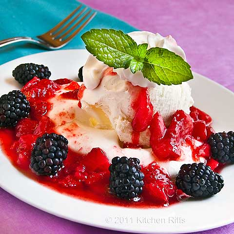 Meringue on plate smothered in ice cream, whipped cream, strawberry sauce, and blackberries with mint garnish