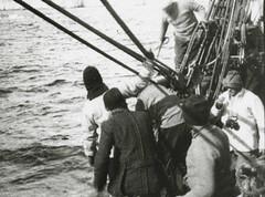Group of men at side of vessel