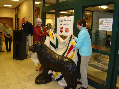 The life-sized statue of Seaman, the famed Newfoundland dog who accompanied the Lewis & Clark expedition, is unveiled at the Lewis & Clark Interpretive Center by (left) Margaret Halko, the widow of the statue's sculptor Joe Halko; and Carol Mungus, whose dog 'Windsor' stood as the model for Halko's creation. (USDA Forest Service photo)