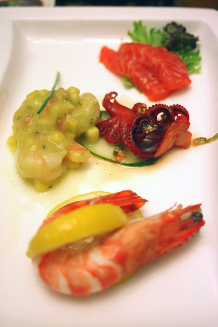 Starters of salmon sashimi, prawn and mango with avocado mousse, baby octopus, and poached tiger prawns