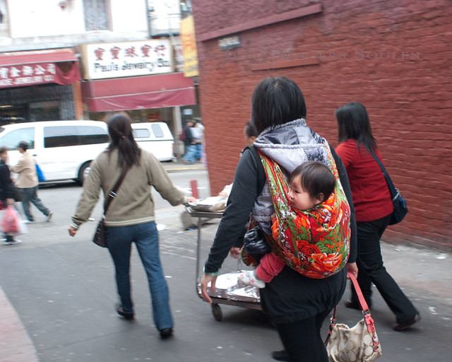A group of women push a cart of food down an alley in Chinatown, one with a baby strapped to her back.