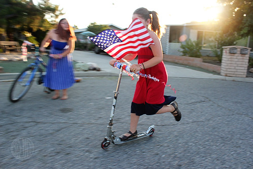 Girl riding a scooter with American flag and streamers