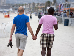 Gay couple holding hands on the beach - by San Diego Shooter