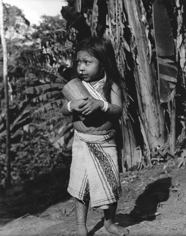 Baxi, a Cashinahua girl with her wooden doll (note the carved eyes and mouth).  The designs painted on her body fade after about a week. Peru, 1957. Photograph by Kenneth M. Kensinger. Penn Museum image #148803