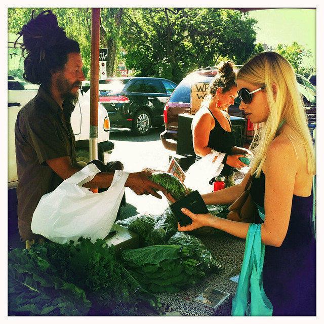 Shanan buying produce from Heliotrope at the Regina Farmers' Market