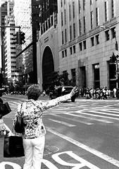 hailing a cab (tapesonthefloor) Tags: street newyorkcity woman shopping arm manhattan cab taxi olympus midtown bags halfframe kodaktmaxdeveloper hailing penfv homeprocessed 38mmf18fzuikoautos nickrflickr