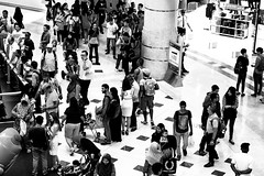 silence in chaos (yangkuo) Tags: needleinthehaystack bw mono crowd event f1 promotional people faces bustling observation activity mzuiko 45mm suria klcc mall