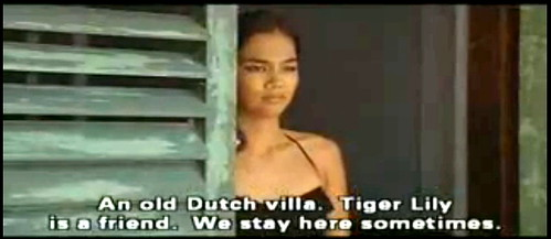 Tiger Lily stands in the door of the old Dutch villa (screenshot from The Year of Living Dangerously)