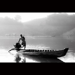 Early morning on Lake Da Mi, Vietnam (-clicking-) Tags: lighting morning light people blackandwhite bw mist mountain lake reflection water monochrome silhouette misty fog sunrise landscape boats dawn blackwhite smog fisherman peace foggy earlymorning peaceful vietnam serene pure nocolors vietnameselandscape hami lakedami