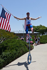 Young man on unicycle with American flag. Peop...