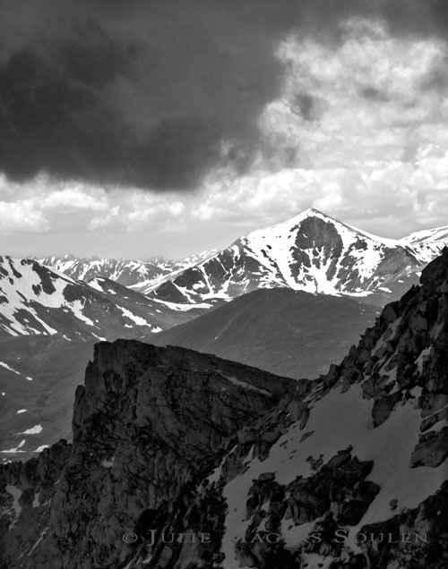 A black and white photo of the rugged Rocky Mountains of Colorado rise up to touch the storm clouds creating matching angles.