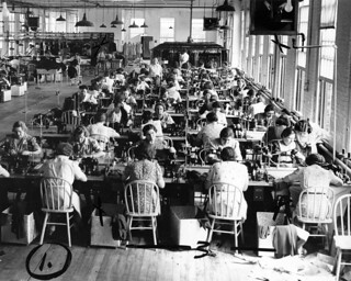 Women sewing at long tables next to tall windows in a garment factory.