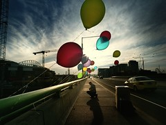 a prayer on a bridge (mugley) Tags: city bridge blue red summer sky urban man colour green slr 120 mamiya film car yellow architecture clouds buildings mediumformat balloons paul prime evening vanishingpoint 645 fuji photographer crane taxi perspective australia melbourne wideangle victoria scan bin negative string epson docklands railing kneeling 6x45 cloudporn reala goldenhour mamiya645 bloke urbanlandscape lowsun populated longshadows c41 spaceframe latrobest reala100 v700 humanfigure cloudage mamiya645protl conder m645 port1010 docklandsstadium vermininc fujicolorsuperiareala100 35mmf35sekorn etihadstadium melbcompjan2011