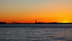 Lady of the Night (Celtics24) Tags: nyc longexposure sunset orange usa ny newyork brooklyn canon landscape unitedstatesofamerica eastriver hudsonriver statueofliberty ladyliberty canon5dmkii