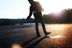 give me a new direction (C.J. Newberry) Tags: light sun silhouette dance movement parkinglot shadows empty flare arrow asphalt treeline
