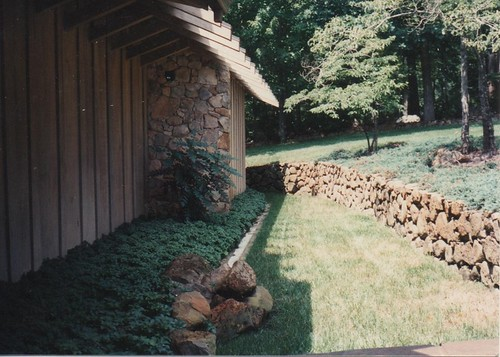 stone walls on the house front with garden supported by stone retaining walls