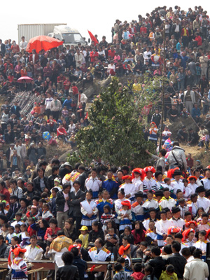 Large crowd in bright costumes gathered on a mountainside