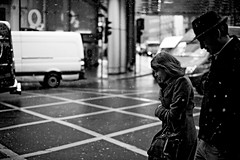 She Smiles in the Snow (Chris JL) Tags: uk winter bw woman snow man london smile hat weather silhouette walking photo crossing candid profiles streetphotography holborn photoderue photographiederue fotografadecalle fotografiadistrada nikkor50mmf14g nikond3s chrisjl shesmilesinthesnow citydreamsbw