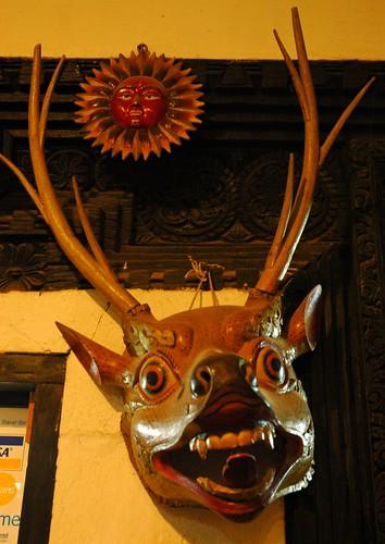 Deer mask, Tibetan style, ritual masquerade, wood, sun, business hallway, Boudha, Kathmandu, Nepal by Wonderlane