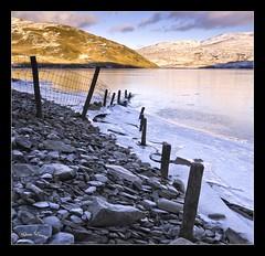 Nant-y-Moch (Adam John Evans Photo) Tags: winter lake snow ice water sunshine wales fence frozen nikon rocks december pebbles hills shore posts ceredigion d300 sigma1020mm nantymoch resrvoir