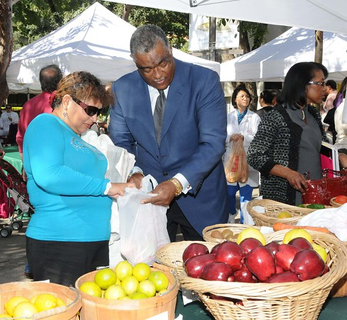 SERO Regional Administrator Don Arnette assists SNAP client Maria Salgado with bagging the fresh fruits and vegetables she purchased at the Jackson Memorial Foundation Green Market, Miami, Fla., with her SNAP benefits.