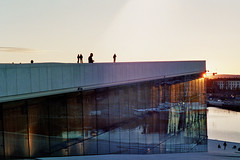 On the Roof of the Oslo Opera House (fairminer) Tags: roof sunset sky people sun reflection slr film water silhouette oslo norway stone architecture analog 35mm evening design norge nikon opera fjord analogue marble marmor operahuset operaen snhetta snohetta osloopera oslooperahouse snhetta