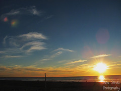 (heysaraaa) Tags: ocean sky people orange sun beach water yellow lens bright flare sloud