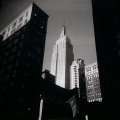ESB (sonofwalrus) Tags: city nyc blackandwhite usa newyork film architecture buildings holga lomo lomography shadows manhattan flag scan esb empirestatebuilding hpc5380