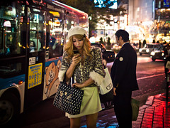 Shibuya  Fashion Victim (adde adesokan) Tags: street travel light woman man color colour bus girl face hat car japan standing pen handy photography gold tokyo uniform mask candid voigtlander shibuya streetphotography style olympus skirt business suit leopard  nippon  nihon voigtlnder 25mm tokio texting f095 1095 streetphotographer m43 095 mft mirrorless microfourthirds theblackstar mirrorlesscamera streettogs