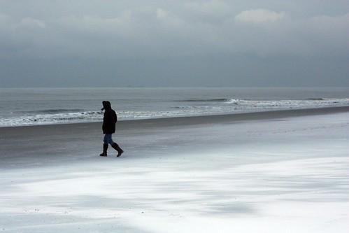 Pessoa encapotada andando na praia nevada de Scheveningen, Holanda
