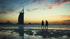 Lazy sunset walk (momentaryawe.com) Tags: sunset sea orange building love beach water reflections walking hotel couple dusk uae middleeast landmark structure emirates burjalarab lowtide luxury d300s catalinmarin momentaryawecom