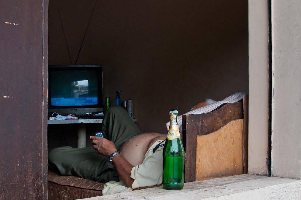 Un Señor mira televisión comodamente desde su cama cerca de la ventana en la calurosa tarde del 24 de Diciembre luego de disfrutar su botella de Sidra (Elton Núñez - Asunción, Paraguay)