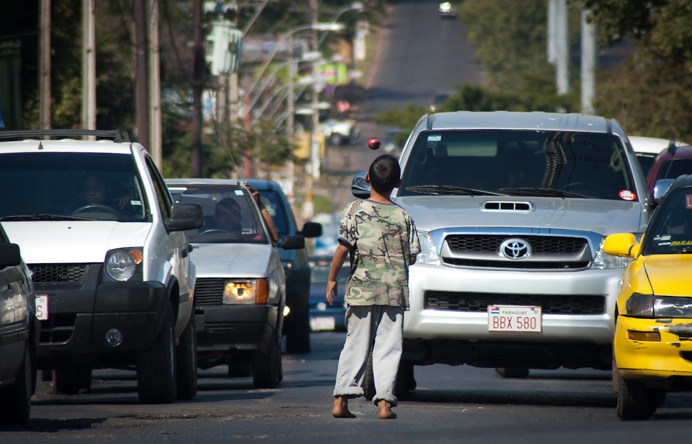 Un Niño se gana la vida haciendo malabarismos con pelotitas durante el semáforo en rojo en el cruce de las Avenidas Luis María Argaña y Perón. (Elton Núñez - Asunción, Paraguay)