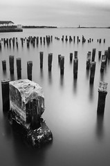 Desolate Seascape I (laverrue) Tags: park nyc longexposure skyline brooklyn pier blackwhite quiet peace sad desert manhattan empty dumbo peaceful explore silence eastriver gothamist statueofliberty desolate tranquil nomansland uncertainty unoccupied governorisland explored