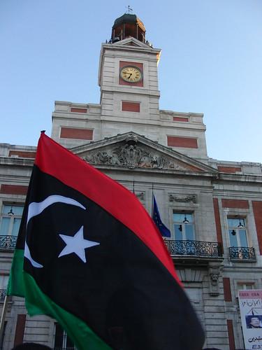 Bandera ondeando frente al reloj de la Puerta del Sol