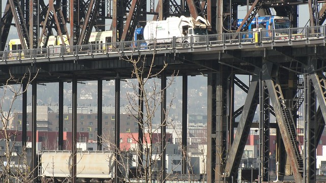 Zoom shot of the Steel Bridge with a freight train crossing the lower deck, and truck and car traffic above