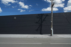 Moorabbin March 2011 (i_shudder) Tags: road shadow abstract wall clouds composition grey pole wires moorabbin 2011