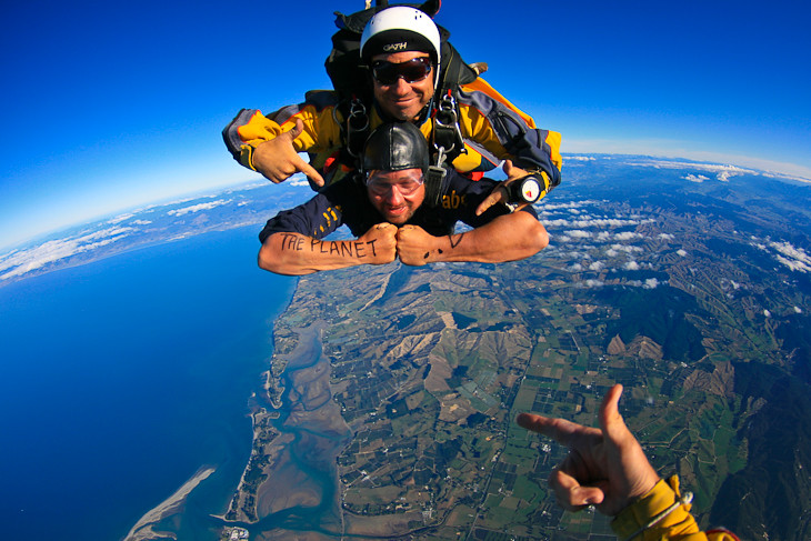 tandem skydiving with writing on arms
